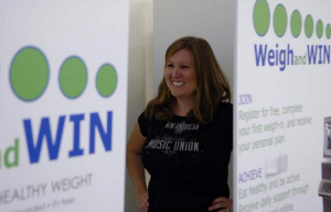 Weigh  and Win participant Cassie Kauffman weighs in on an incentaHEALTH HEALTHspot kiosk